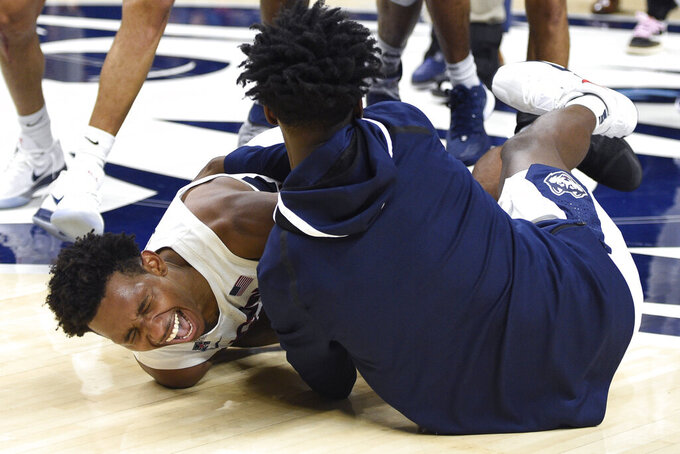 Connecticut's Christian Vital, left, is pulled to the court and hugged by Connecticut's Temi Aiyegbusi, right, at the end of an NCAA college basketball game, Thursday, March 5, 2020, in Storrs, Conn. (AP Photo/Jessica Hill)