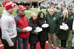 Nebraska head coach Scott Frost, left, Gerald and Jill Foltz, Karen Sadler, third right, Michigan State head coach Mark Dantonio, second from right, and Katie Sadler, right, participate in a midfield ceremony before an NCAA college football game in Lincoln, Neb., Saturday, Nov. 17, 2018. The ceremony was held to honor former punters Sam Foltz, of Nebraska, and Mike Sadler, of Michigan State, who died in a car accident in July 2016 while both were in Wisconsin to work at a kicking camp. It is the first game between the teams since the accident. (AP Photo/Nati Harnik)