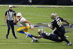 Los Angeles Chargers quarterback Justin Herbert scrambles under pressure from Los Angeles Chargers running back Joshua Kelley and defensive end Cameron Jordan (94) in the first half of an NFL football game in New Orleans, Monday, Oct. 12, 2020. (AP Photo/Butch Dill)