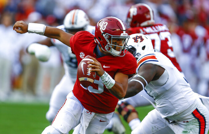 Alabama quarterback Tua Tagovailoa (13) escapes pressure from Auburn defensive lineman Marlon Davidson (3) during the first half of an NCAA college football game, Saturday, Nov. 24, 2018, in Tuscaloosa, Ala. (AP Photo/Butch Dill)