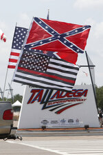 Race fans fly Confederate battle flags and United States flags as they drive by the entrance to Talladega Superspeedway prior to a NASCAR Cup Series auto race in Talladega Ala., Sunday, June 21, 2020. (AP Photo/John Bazemore)