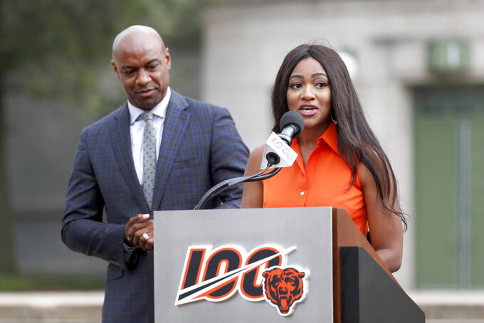 Brittney Payton, daughter of former Chicago Bears and Pro Football Hall of Fame running back Walter Payton, and her brother Jarrett, address the crowd during a unveiling ceremony outside Soldier Field of statues honoring George Halas and their father Tuesday, Sept. 3, 2019, in Chicago. (AP Photo/Charles Rex Arbogast)