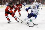 New Jersey Devils' Taylor Hall (9) fights for control of the puck with Vancouver Canucks' Quinn Hughes (43) during the first period of an NHL hockey game Saturday, Oct. 19, 2019, in Newark, N.J. (AP Photo/Frank Franklin II)