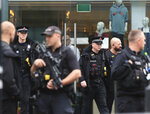 Armed police officers outside the Arndale Centre in Manchester, England, Friday Oct. 11, 2019, after a stabbing incident at the shopping center that left four people injured. Greater Manchester Police say a man in his 40s has been arrested on suspicion of serious assault. He had been taken into custody. (Peter Byrne/PA via AP)