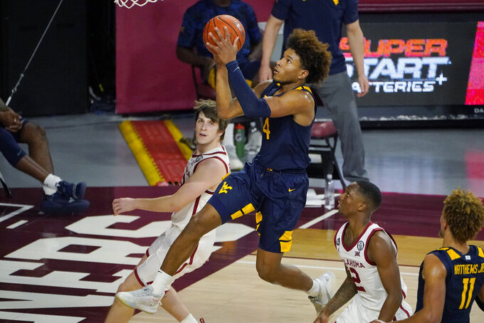 West Virginia guard Miles McBride, center, goes to the basket between Oklahoma guard Austin Reaves, left, and guard Umoja Gibson (2) in the second half of an NCAA college basketball game Saturday, Jan. 2, 2021, in Norman, Okla. (AP Photo/Sue Ogrocki)