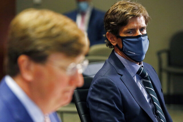 Mississippi State Health Officer Dr. Thomas Dobbs, right, listens as Gov. Tate Reeves responds to a reporter's question regarding his executive order mandating that all adults and students wear masks in schools, unless there's a medical reason that prevents them from doing so, during the governor's COVID-19 press briefing in Jackson, Miss., Tuesday, Aug. 4, 2020. State officials provided reporters an update on the coronavirus and the state's ongoing strategy to limit transmission in public schools. (AP Photo/Rogelio V. Solis)