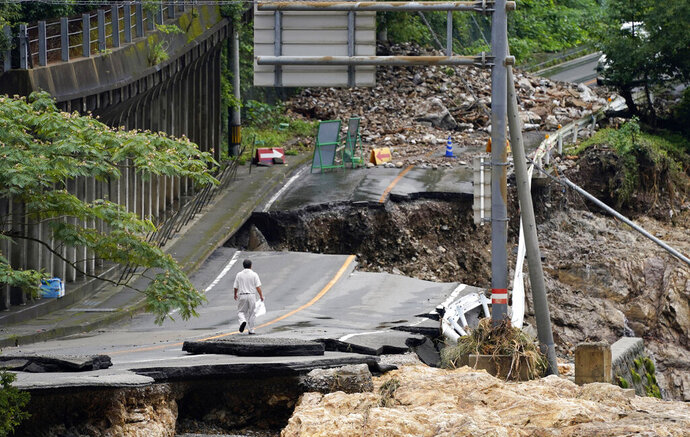 A man walks on heavily damaged road following a heavy rain in Kumamura, Kumamoto prefecture, southern Japan Monday, July 6, 2020. Rescue operations continued and rain threatened wider areas of the main island of Kyushu. (Koji Harada/Kyodo News via AP)