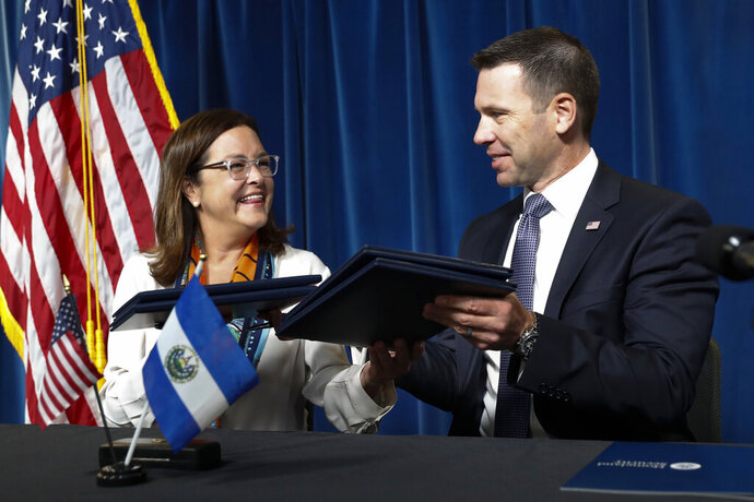 Acting Secretary of Homeland Security Kevin McAleenan exchanges folders with El Salvador Foreign Affairs Minister Alexandra Hill after signing an agreement during news conference at the U.S. Customs and Border Protection headquarters in Washington, Friday, Sept. 20, 2019.  (AP Photo/Pablo Martinez Monsivais)