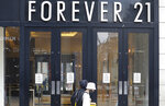 People walk past a branch of Forever 21, in London, Thursday, July 16, 2020. Unemployment across the U.K. has held steady during the coronavirus lockdown as a result of a government salary support scheme, but there are clear signals emerging that job losses will skyrocket over coming months. The Office for National Statistics said Thursday there were 649,000 fewer people, or 2.2%, on payroll in June when compared with March when the lockdown restrictions were imposed. (AP Photo/Alastair Grant)