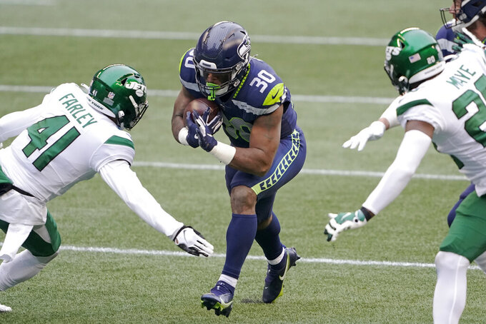 Seattle Seahawks running back Carlos Hyde (30) runs with the ball between New York Jets' Matthias Farley (41) and Marcus Maye during the first half of an NFL football game, Sunday, Dec. 13, 2020, in Seattle. (AP Photo/Ted S. Warren)