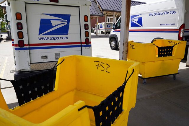 Mail delivery vehicles are parked outside a post office in Boys Town, Neb., Tuesday, Aug. 18, 2020. The Postmaster general announced Tuesday he is halting some operational changes to mail delivery that critics warned were causing widespread delays and could disrupt voting in the November election. Postmaster General Louis DeJoy said he would