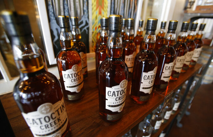 FILE - In this June 20, 2018 file photo, Catoctin Creek Distillery whiskey is on display in a tasting room in Purcellville, Va.  Retaliatory tariffs caused a sharp downturn in American whiskey exports in the last half of 2018 as distillers started feeling the pain from getting caught up in global trade disputes, an industry trade group said Tuesday, Feb. 12, 2019. Catoctin Creek Distillery has a couple hundred cases of its rye whiskey sitting in a European warehouse. The inventory was built up in anticipation of growing European sales in 2018. But since the tariffs took effect, their sales in Italy and Germany have plunged, and its plans of expanding to the United Kingdom are on hold, said its co-founder and general manager, Scott Harris. (AP Photo/Steve Helber, File)