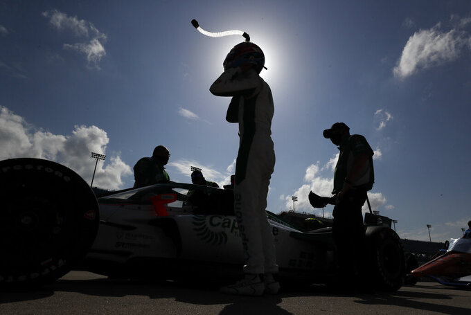 Colton Herta, center, puts on his helmet on during qualifying for an IndyCar Series auto race Friday, July 17, 2020, at Iowa Speedway in Newton, Iowa. (AP Photo/Charlie Neibergall)