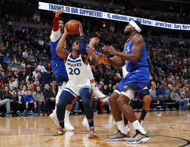 Minnesota Timberwolves guard Josh Okogie, front left, pulls in a rebound as Denver Nuggets forward Paul Millsap, front right, and guards Jamal Murray, back left, and Gary Harris defend in the first half of an NBA basketball game Friday, Dec. 20, 2019, in Denver. (AP Photo/David Zalubowski)