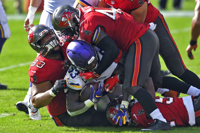 Tampa Bay Buccaneers defensive end Ndamukong Suh (93) and inside linebacker Devin White (45) team up to stop Minnesota Vikings running back Dalvin Cook (33) during the first half of an NFL football game Sunday, Dec. 13, 2020, in Tampa, Fla. (AP Photo/Jason Behnken)