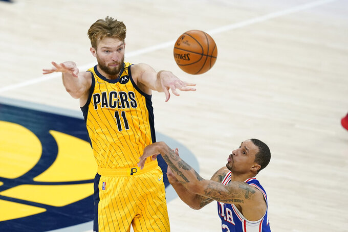 Indiana Pacers' Domantas Sabonis (11) makes a pass against Philadelphia 76ers' George Hill (33) during the second half of an NBA basketball game, Tuesday, May 11, 2021, in Indianapolis. Indiana won 103-94. (AP Photo/Darron Cummings)