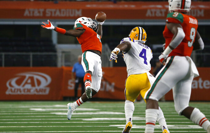 Miami wide receiver Jeff Thomas, left, makes a one-handed catch for a first down in front of LSU linebacker K'Lavon Chaisson, second from right, during the first half of an NCAA college football game Sunday, Sept. 2, 2018, in Arlington, Texas. (AP Photo/Ron Jenkins)