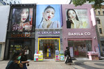 """People pass by cosmetics shops at a shopping street, July 3, 2020, in Seoul, South Korea. In the wake of mass protests against racial injustice in the U.S., these corporations are re-branding their skin lightening products in Africa, Asia and the Middle East, but for generations of women raised on their messaging, the new marketing is unlikely to reverse deeply rooted prejudices around """"colorism"""", the idea that fair skin is better than dark skin. (AP Photo/Ahn Young-joon)"""