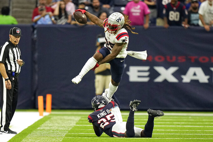 New England Patriots running back Brandon Bolden, top, leaps over Houston Texans cornerback Desmond King II during the second half of an NFL football game Sunday, Oct. 10, 2021, in Houston. (AP Photo/Eric Christian Smith)