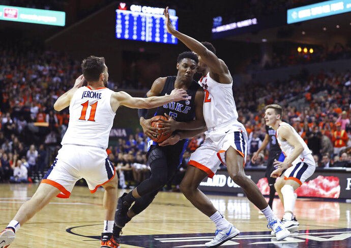 Duke forward RJ Barrett (5) splits two Virginia defenders during the first half of an NCAA college basketball game Saturday, Feb. 9, 2018, in Charlottesville, Va. (AP Photo/Zack Wajsgras)