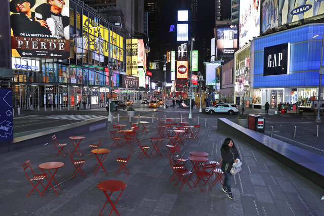 FILE - This March 16, 2020 file photo shows a woman walking through a lightly trafficked Times Square in New York. COVID-19 has shaken theater fans and shuttered all New York City's venues, including Broadway, which grossed $1.8 billion last season and attracted a record 15 million people. How Broadway — one the city's jewels — will reopen is still not clear. (AP Photo/Seth Wenig, FIle)