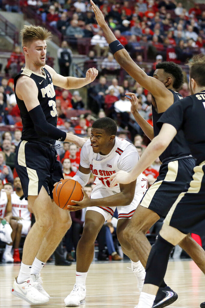 Ohio State's E.J. Liddell, center, tries to get a shot off between Purdue's Matt Haarms, left, and Aaron Wheeler during the second half of an NCAA college basketball game Saturday, Feb. 15, 2020, in Columbus, Ohio. Ohio State beat Purdue 68-52. (AP Photo/Jay LaPrete)