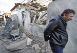 A man walks past a shop damaged by shelling by Azerbaijan's artillery at a market in Stepanakert, the separatist region of Nagorno-Karabakh, Saturday, Oct. 31, 2020. Nagorno-Karabakh authorities said Azerbaijani military targeted a street market in Stepanakert and residential areas of Shushi on Saturday in violation of a mutual pledge not to target residential areas made after talks in Geneva. (AP Photo)