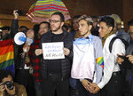 Esteban Carrillo, 24, second from right, holds hands with Nicolas Tellez, 19, during a