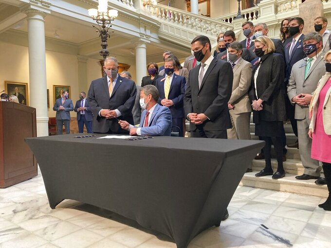 Georgia Gov. Brian Kemp, seated, hands a pen to Georgia House Speaker David Ralston on Monday, March 22, 2021, at the state capitol in Atlanta after signing a tax cut bill. The measure would raise the amount of money someone can earn before paying state income taxes, saving most individual filers up to $43. (AP Photo/Jeff Amy)