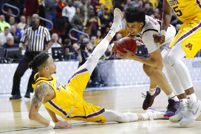 Minnesota guard Amir Coffey, left, is fouled by Louisville forward Jordan Nwora during a first round men's college basketball game in the NCAA Tournament, Thursday, March 21, 2019, in Des Moines, Iowa. (AP Photo/Charlie Neibergall)