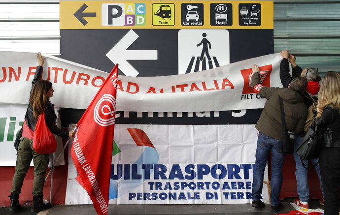 Striking Alitalia workers place unions flags and banners, at the Fiumicino airport in Rome Tuesday, May 21, 2019. Alitalia workers are on a 24 hours strike since Monday night. (AP Photo/Alessandra Tarantino)