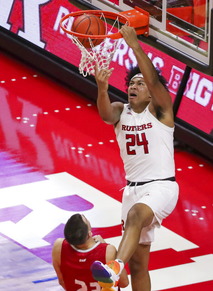 Rutgers guard Ron Harper Jr. (24) dunks over Sacred Heart forward Matas Spokas (23) during the first half of an NCAA college basketball game Wednesday, Nov. 25, 2020, in Piscataway, N.J. (Andrew Mills/NJ Advance Media via AP)