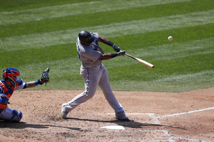 Miami Marlins' Jesus Aguilar, right, hits a fifth-inning solo home run during a baseball game against the New York Mets at Citi Field, Sunday, Aug. 9, 2020, in New York. (AP Photo/Kathy Willens)