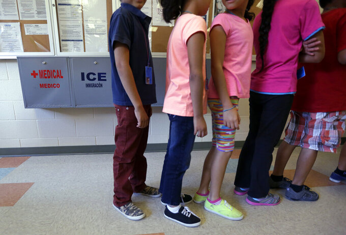 FILE - In this Sept. 10, 2014 file photo, detained immigrant children line up in the cafeteria at the Karnes County Residential Center, a temporary home for immigrant women and children detained at the border, in Karnes City, Texas. President Joe Biden's administration on Friday, March 5, 2021 instructed long-term facilities that hold immigrant children to lift capacity restrictions enacted during the coronavirus pandemic to open up much-needed beds in a system facing sharply increasing needs. (AP Photo/Eric Gay, File)