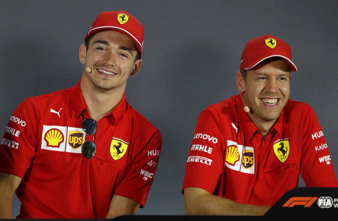 Ferrari driver Charles Leclerc of Monaco, left, is flanked by his teammate Sebastian Vettel of Germany during a press conference at the Monza racetrack, in Monza, Italy , Thursday, Sept.5, 2019. The Formula one race will be held on Sunday. (AP Photo/Luca Bruno)
