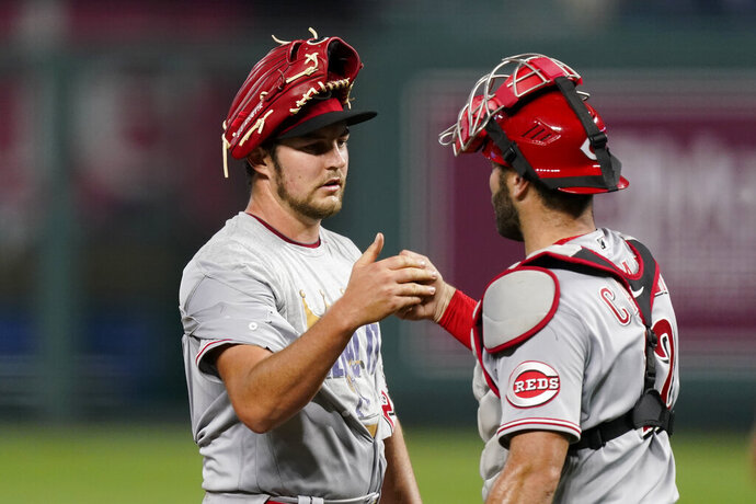 Cincinnati Reds starting pitcher Trevor Bauer and catcher Curt Casali celebrate after game two of a baseball doubleheader against the Kansas City Royals Wednesday, Aug. 19, 2020, in Kansas City, Mo.  (AP Photo/Charlie Riedel)