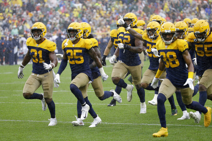 Members of the Green Bay Packers celebrate after an incomplete pass call was reviewed by officials and ruled an interception by Green Bay Packers defensive back Darnell Savage during the second half of an NFL football game against the Denver Broncos Sunday, Sept. 22, 2019, in Green Bay, Wis. (AP Photo/Mike Roemer)