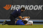 A fan who made her way on to the field is tackled by security personnel during a baseball game between the Arizona Diamondbacks and the Los Angeles Dodgers Wednesday, Sept. 15, 2021, in Los Angeles. (AP Photo/Ashley Landis)