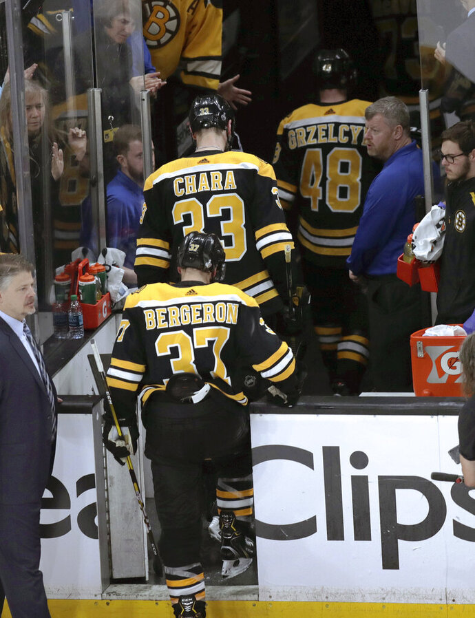 Boston Bruins' Patrice Bergeron (37), Zdeno Chara (33), of Slovakia, and Matt Grzelcyk (48) leave the ice after the St. Louis defeated the Bruins in Game 7 of the NHL hockey Stanley Cup Final, Wednesday, June 12, 2019, in Boston. (AP Photo/Charles Krupa)