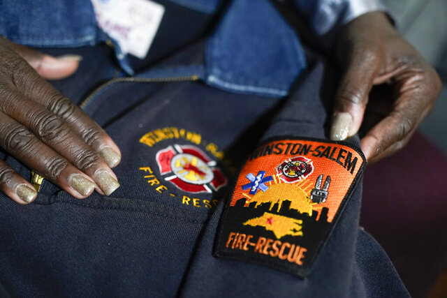 Timika Ingram holds a jacket she had when she was a firefighter on Thursday, Nov. 19, 2020, in Charlotte, N.C. A group of Black firefighters in a North Carolina city have filed a grievance over conditions they have endured for more than 30 years. (AP Photo/Chris Carlson)