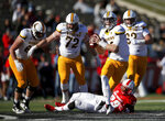 Wyoming quarterback Tyler Vander Waal (18) throws a pass after evading the tackle by New Mexico linebacker Jordan Flack (29) during the first half of an NCAA college football game in Albuquerque, N.M., Saturday, Nov. 24, 2018. (AP Photo/Andres Leighton)