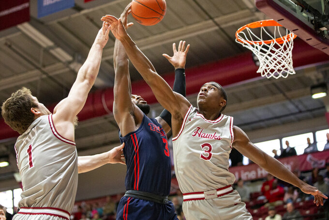 Saint Joseph's guards Ryan Daly (1) and Cameron Brown, right, try to block a shot by Dayton guard Trey Landers, center, during the first half of an NCAA college basketball game, Sunday, Jan. 5, 2020, in Philadelphia. (AP Photo/Laurence Kesterson)