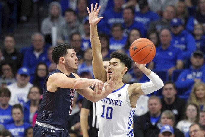 Fairleigh Dickinson's Bassel Saliba Jr. passes the ball away from Kentucky's Johnny Juzang (10) during the second half of an NCAA college basketball game in Lexington, Ky., Saturday, Dec. 7, 2019. (AP Photo/James Crisp)