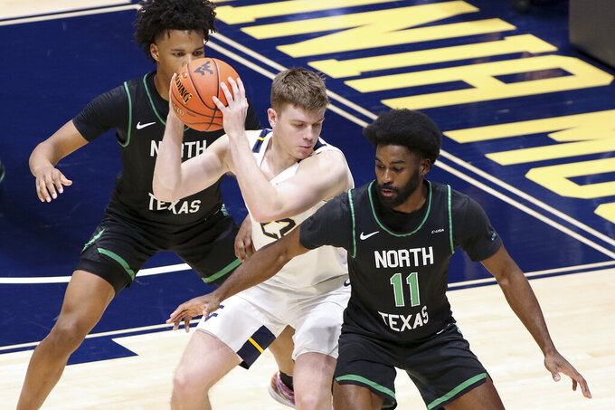 West Virginia guard Sean McNeil (22) is defended by North Texas guards Rubin Jones (15) and JJ Murray (11) during the second half of an NCAA college basketball game Friday, Dec. 11, 2020, in Morgantown, W.Va. (AP Photo/Kathleen Batten)