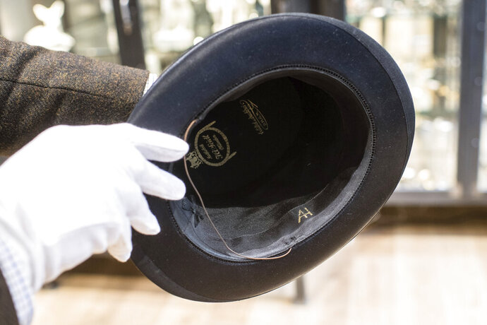 """A man holds a hat with the initials of Adolf Hitler prior to an auction in Grasbrunn, Germany, Wednesday, Nov. 201, 2019. A Jewish group has sharply condemned an auction of Nazi memorabilia in Germany. The European Jewish Association condemned the auction Wednesday at Hermann Historica in Munich, saying that """"it's wrong to make money off these blood-soaked items, especially in Germany of all places"""