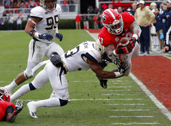 Georgia running back Elijah Holyfield (13) dives past Georgia Tech defensive back Jaytlin Askew (33) to score a touchdown during the first half of an NCAA college football game Saturday, Nov. 24, 2018, in Athens, Ga. (AP Photo/John Bazemore)