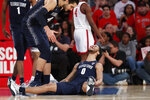 Georgetown center Omer Yurtseven (44) leans over to help up teammate Jahvon Blair (0) who reacts after earning a free throw during the second half of an NCAA college basketball game against St. John's, Sunday, Feb. 2, 2020, in New York. (AP Photo/Kathy Willens)