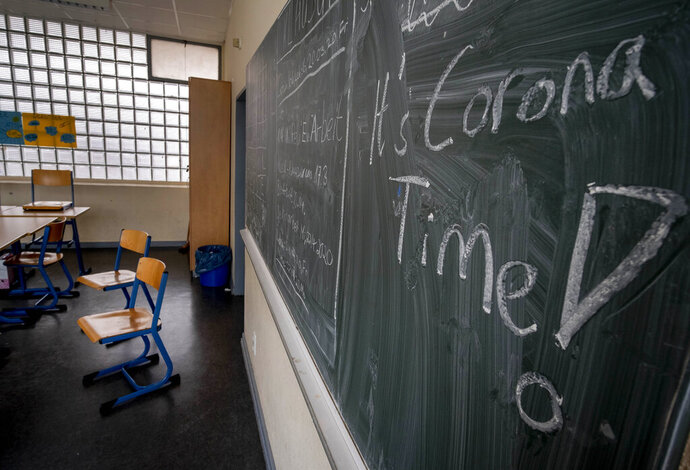 FILE - In this Friday, March 13, 2020 file photo the slogan 'It's Corona Time' is written on the chalkboard of an empty classroom of a high school in Frankfurt, Germany. The German government on Wednesday agreed on a strategy to boost the use of data for commercial purposes and signed a deal with state education authorities to fund laptops for teachers who have to work from home because of the virus lockdown. (AP Photo/Michael Probst, file)