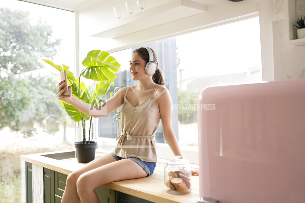 Young woman taking selfie while listening music through headphones in kitchen at home