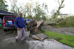 Marcus Peterson walks past a downed tree in his yard after Hurricane Delta moved through, Saturday, Oct. 10, 2020, in Jennings, La. Delta hit as a Category 2 hurricane with top winds of 100 mph (155 kph) before rapidly weakening over land. (AP Photo/Gerald Herbert)